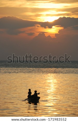 Sunset in mabul island with kids pedalling small boat  silhouette.Sabah, Malaysia - stock photo