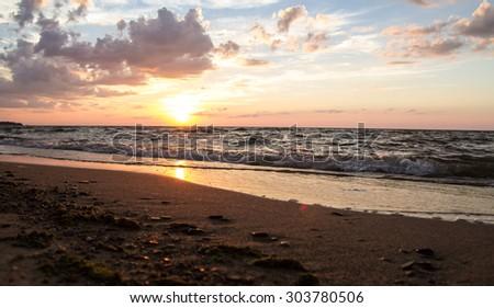 Sunset In Paradise. Gorgeous sunset reflects off the Lake Huron horizon. Port Crescent State Park. Port Austin, Michigan. - stock photo