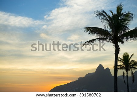Sunset in Rio de Janeiro Ipanema Beach Brazil with Two Brothers Dois Irmaos Mountain and palm trees silhouettes - stock photo