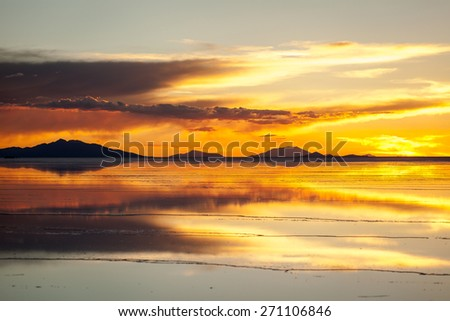 Sunset in salar de Uyuni. Reflection of the clouds in the wet surface of salt. Mountain background - stock photo
