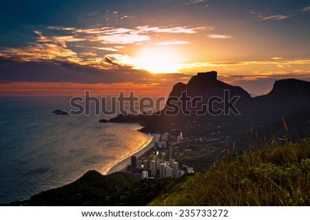 Sunset in Sao Conrado Beach in Rio de Janeiro, Surrounded by Mountains, the Sun is Going Down Behind the Pedra da Gavea Rock - stock photo