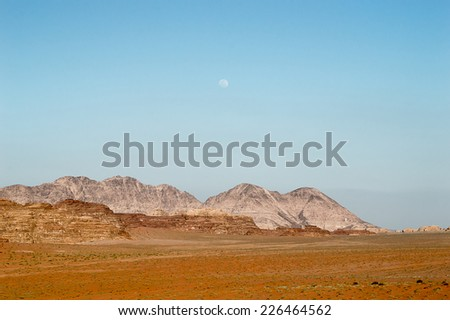 sunset in the desert of Wadi Rum with moon background - stock photo