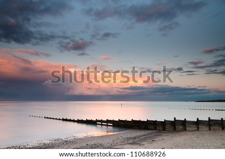Sunset in the east / Western sunset shining on easterly clouds at Blyth beach - stock photo