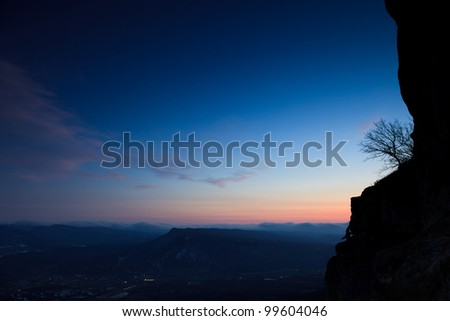 Sunset in the mountains and a tree on a rock in the foreground - stock photo