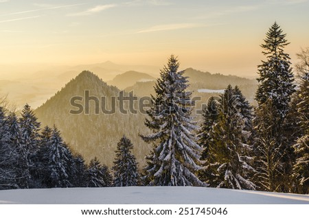 Sunset in the mountains with golden mist. - stock photo