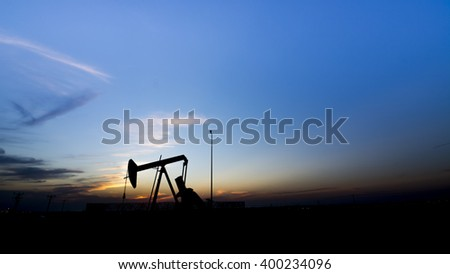 Sunset in the oil field - Silhouette of crude oil pump - Bahrain  - stock photo