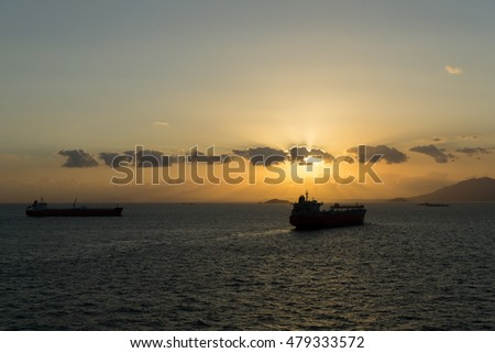 Sunset in the sea over two ships.