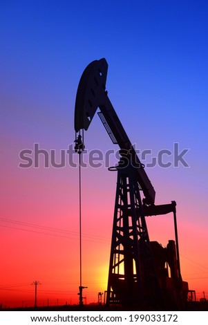 Sunset is a job of the pumping unit in oil field   - stock photo