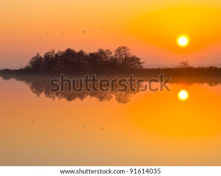 Sunset is reflecting in mirror like lake - stock photo
