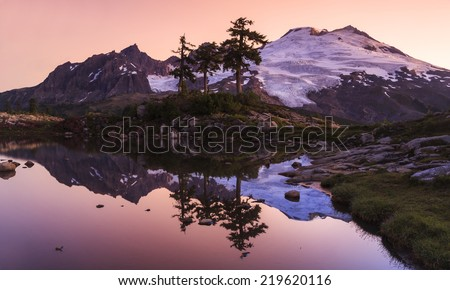 Sunset landscape of a snowy mountain peak reflecting  of a small pond - stock photo