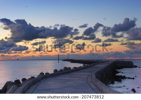 Sunset landscape of the shore of Baltic sea with dark lowering clouds and zigzag pier - stock photo