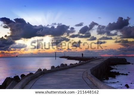 Sunset landscape of the shore of Baltic sea with dark lowering clouds,sunbeams and zigzag pier with walking alone man - stock photo
