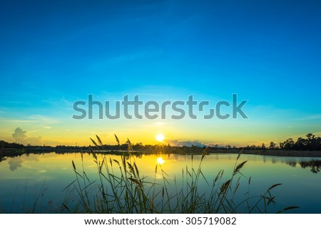Sunset landscape with blue sky at the calm lake - stock photo