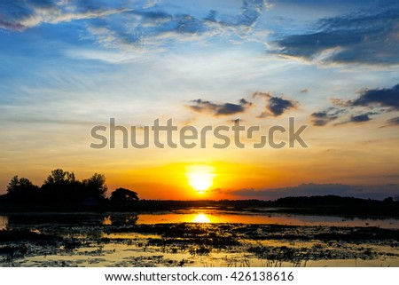 Sunset landscape with blue sky over the calm lake.