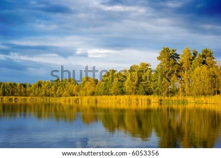 Sunset light falling on the lakeside. Mazury, Poland. - stock photo
