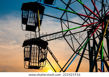 Sunset light on a Ferris wheel at a carnival - stock photo