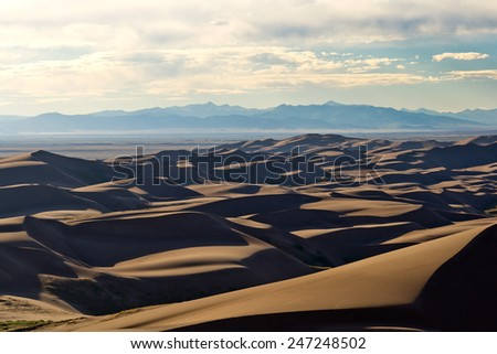 Sunset light shines across Great Sand Dunes National Park in Colorado - stock photo