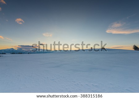 sunset mood at snow meadow with glowing sky in winter - stock photo