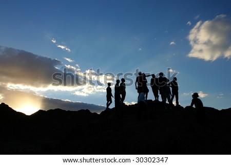 sunset mountains siluyuty people - stock photo