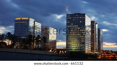sunset office park buildings, a flight flying over a building - stock photo