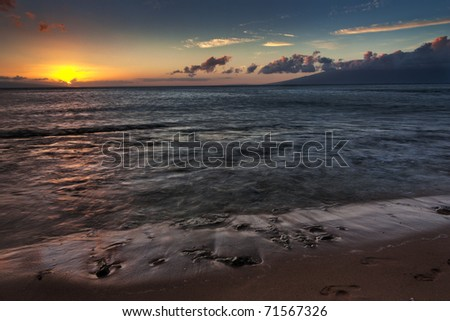 Sunset on a beach on Kaanapali Maui Hawaii showing the colorful sky colors with the island do f Molokai in the distance - stock photo