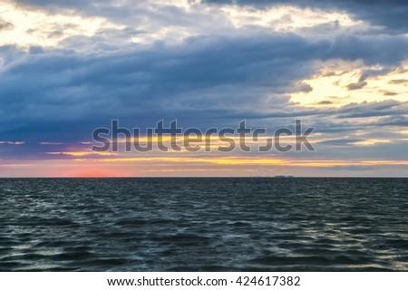 Sunset on a cloudy sky on the coast - stock photo
