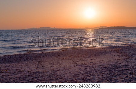 Sunset on a deserted sandy beach with views of the distant islands. - stock photo