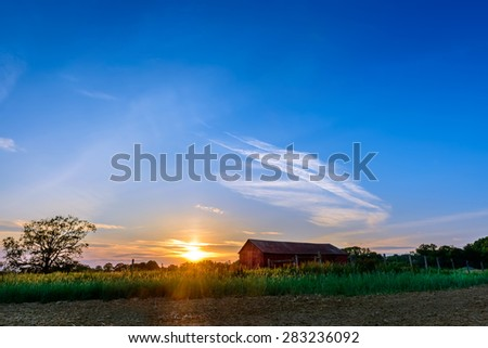 Sunset on a farm in Maryland with plowed field and red barn - stock photo