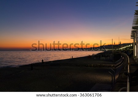 Sunset on a Mediterranean beach in the French Riviera with view of promenade and unidentifiable people walking in the distance