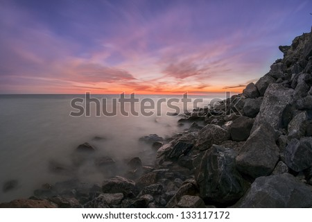 Sunset on a rocky coast - stock photo