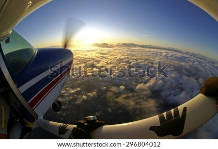 Sunset on a skydive plane above the clouds. Effect made with a fish-eye lens. Photographer hangs on the airplane wing. - stock photo