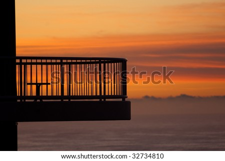 Sunset on Australia's Gold Coast, with apartment balcony in foreground. - stock photo