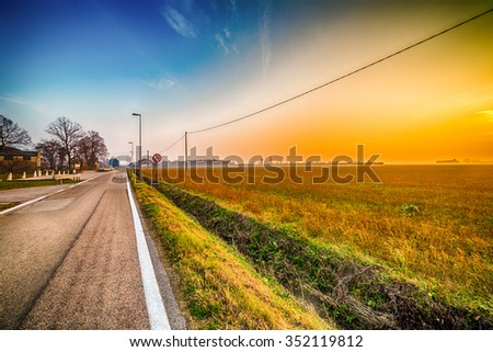 sunset on country road with speed limit signal
