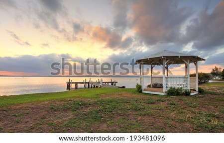 Sunset on Lake Macquarie with jetty and white lattice gazebo in view  Focus to foreground and gazebo, distance and background is not in focus - stock photo