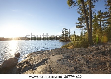 Sunset on lake with rocky shore in northern Minnesota - stock photo