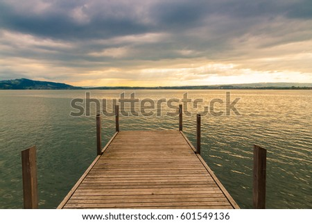 Sunset on lake with wooden pier on overcast day. Zug, Switzerland.