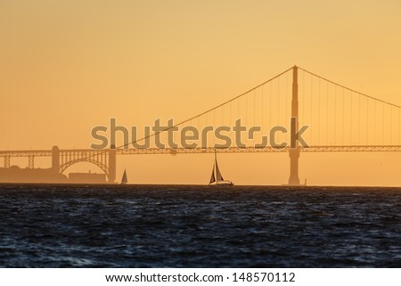 Sunset on San Francisco Bay looking toward the Golden Gate Bridge with two sailboats silhouetted against golden sky - stock photo