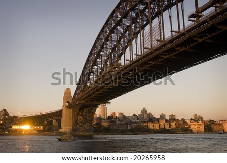 Sunset on Sydney harbour with water taxi passing below the Harbour Bridge - stock photo