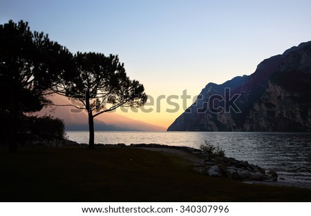 Sunset on the background of the lake surrounded by mountains  - stock photo