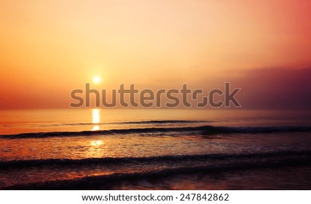 Sunset on the beach with wave of sea, blurred