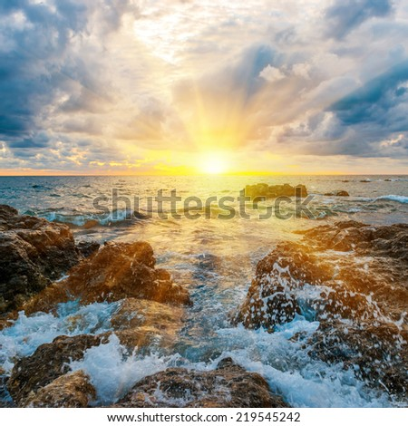 Sunset on the beach with waves, sea, rocks and dramatic sky - stock photo