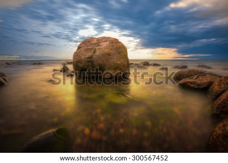 Sunset on the coast of the Estonia ,Tallinn at dawn with rocks in foreground - stock photo