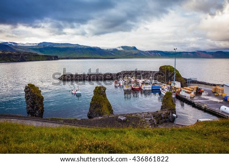 Sunset on the fjord in Iceland. White and red fishing boat in the harbor pier village Arnastapi - stock photo