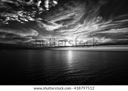 Sunset on the horizon at sea, black and white