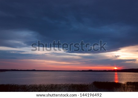 Sunset on the lake against the sky in the clouds. - stock photo