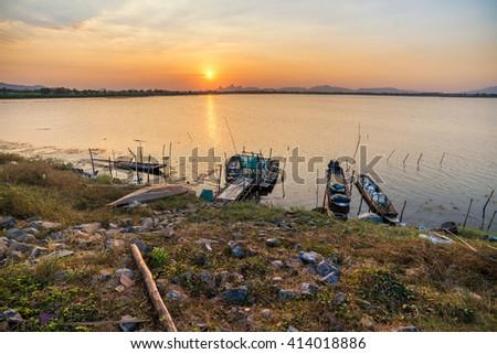 Sunset on the lake, fishing boat on the shore - stock photo
