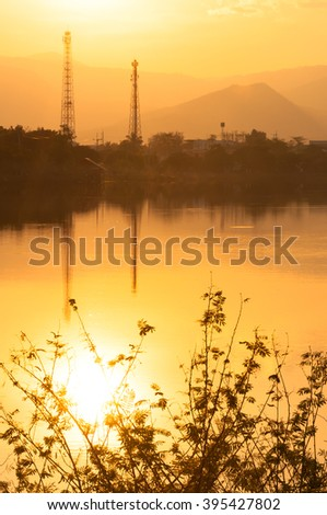 Sunset on the Lake in misty  with electricity lines in background - stock photo