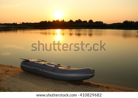 Sunset on the lake with a rubber boat on the shore in Central Russia. - stock photo