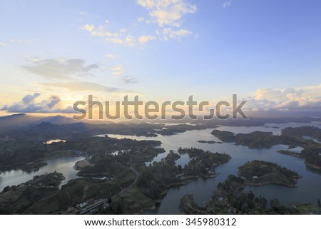 Sunset on the lakes and islands in Guatape taken from Piedra el Penol with blue sky, near Medellin, Colombia. - stock photo