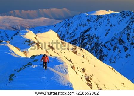 Sunset on the mountain with mountaineer walking on a snowy ridge  - stock photo